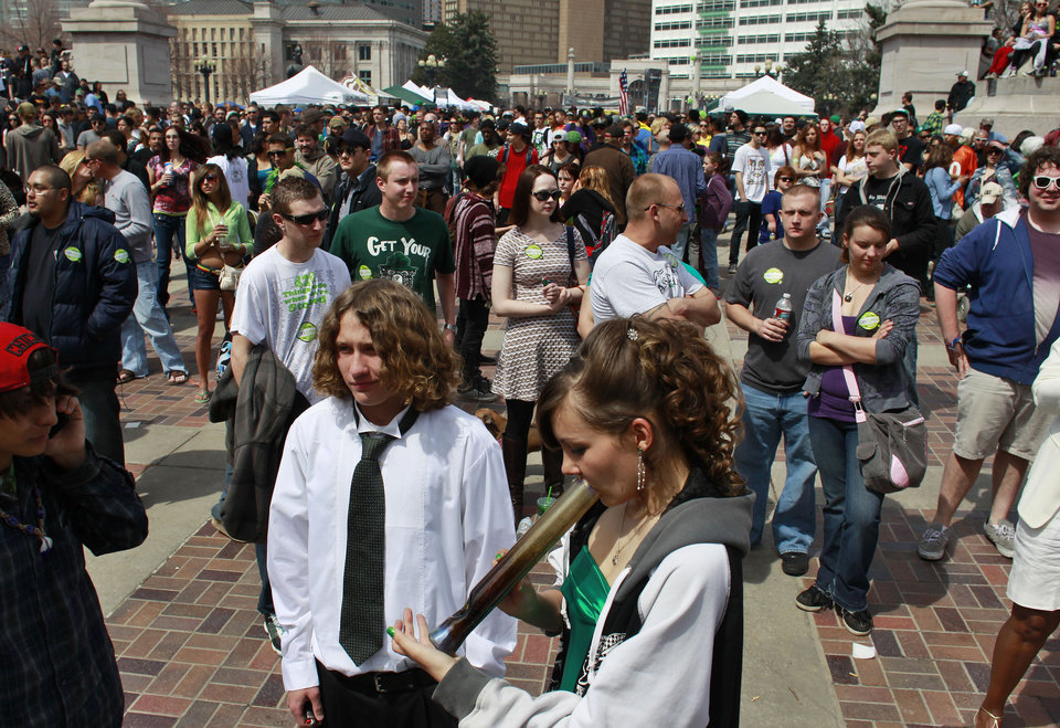 Photo - Youths smoke marijuana at the Denver 4/20 pro-marijuana rally at Civic Center Park in Denver, Saturday, April 20, 2013. Even before the passage in November 2012 of Colorado Amendment 64, which promised the legalization of marijuana for recreational use, April 20th has for years been a celebration of marijuana counterculture, and the 2013 rally was expected to draw larger crowds than previous years. (AP Photo/Brennan Linsley)