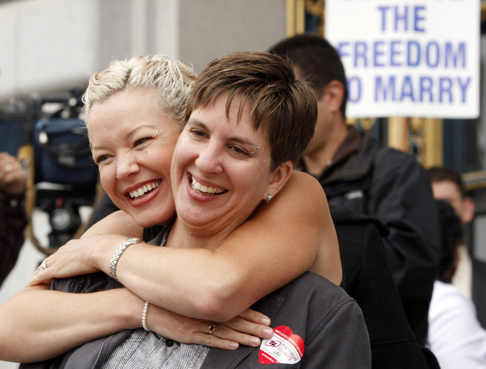 Photo - In this file photo from Aug. 12, 2010, gay couple Tara Walsh, left, and Wen Minkoff embrace outside City Hall in San Francisco. The U.S. Supreme Court decided Friday, Dec. 7, 2012, to hear the appeal of a ruling that struck down Proposition 8, the state's measure that banned same sex marriages. The highly anticipated decision by the court means same-sex marriages will not resume in California any time soon. The justices likely will not issue a ruling until spring of next year. A federal appeals court ruled in February that Proposition 8's ban on same-sex marriage was unconstitutional. But the court delayed implementing the order until same-sex marriage opponents proponents could ask the U.S. Supreme Court to review the ruling. (AP Photo/Ben Margot)