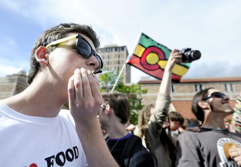 Photo -   Joe, last name not given, at left, smokes a marijuana cigarette in the crowd during the 4/20 rally on the University of Colorado campus in Boulder, Colo., on Friday, April 20, 2012. Many students at the University of Colorado and other campuses across the country have long observed 4/20. The counterculture observation is shared by marijuana users from San Francisco's Golden Gate Park to New York's Greenwich Village. (AP Photo/The Daily Camera, Jeremy Papasso)
