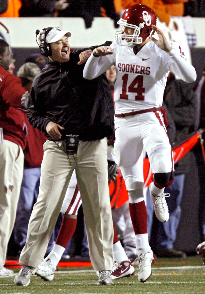 Oklahoma's Sam Bradford (14) and quarterback coach Josh Heupel celebrate after a touchdown during the second half of the college football game between the University of Oklahoma Sooners (OU) and Oklahoma State University Cowboys (OSU) at Boone Pickens Stadium on Saturday, Nov. 29, 2008, in Stillwater, Okla. STAFF PHOTO BY CHRIS LANDSBERGER