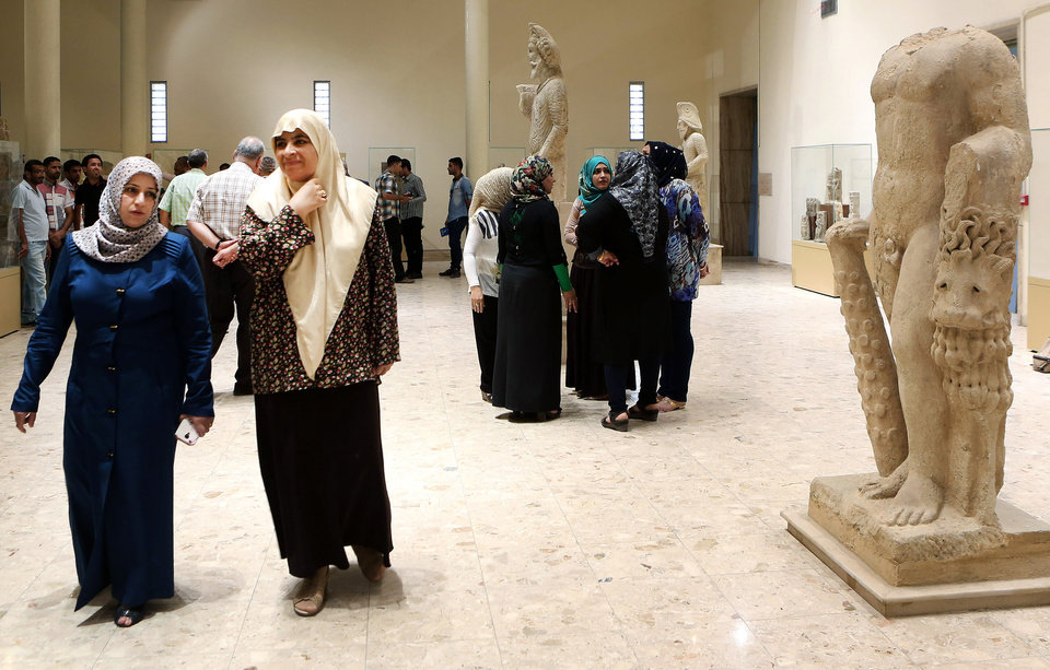Photo - People visit the Iraqi National Museum after two halls were renovated, in Baghdad, Iraq, Thursday, Aug 21, 2014. Two renovated halls adorned mainly with rare life-size stone statues were inaugurated at the Iraqi National Museum on Thursday geared toward honoring the 5,000 year legacy of the ancient city of Hatra. (AP Photo/Hadi Mizban)
