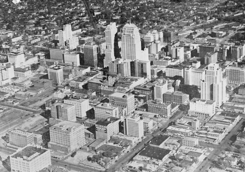 OKLAHOMA CITY / SKY LINE / OKLAHOMA / AERIAL VIEWS / AERIAL PHOTOGRAPHY / AIR VIEWS: A view of downtown Oklahoma City, December 15, 1931. At the lower left corner will be observed undeveloped land vacated a few months ago by the Rock Island and Frisco Railroads. This strip of land, now owned by the city, runs through the entire business district and is to be developed into a beautiful civic center, where an auditorium, library building, art museum, City Hall and other municipal buildings are to be constructed, surrounded by beautiful landscaping, parks and trees. Photo dated 12/15/1931 and published in an Oklahoma City Chamber of Commerce trade publication.