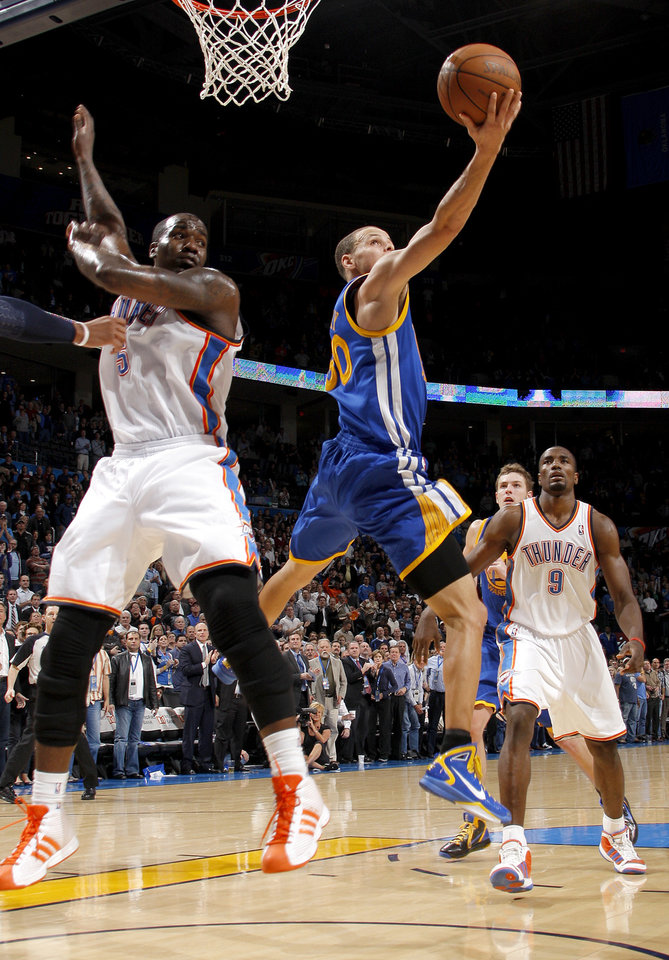 Photo - Golden State's Stephen Curry (30) goes to the basket between Oklahoma City's Kendrick Perkins (5) and Oklahoma City's Serge Ibaka (9) during the NBA basketball game between the Oklahoma City Thunder and the Golden State Warriors at the Oklahoma City Arena, Tuesday, March 29, 2011. Photo by Bryan Terry, The Oklahoman