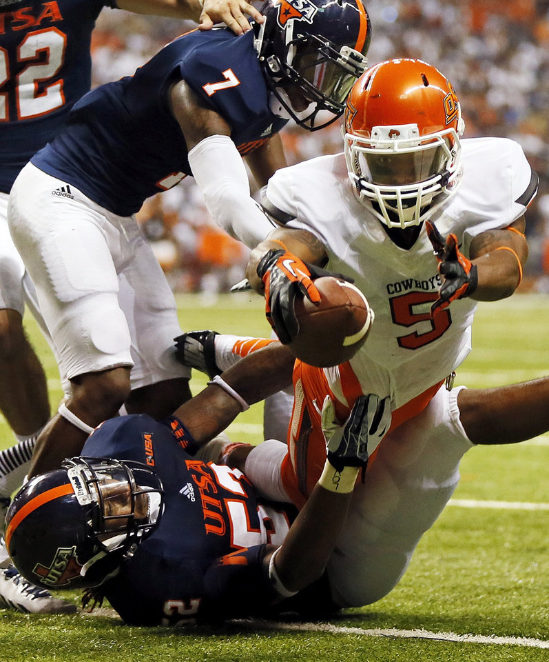 Photo - OSU's Josh Stewart (5) leaps for a touchdown between UTSA's Triston Wade (7) and Blake Terry (52) in the second quarter during a college football game between the University of Texas at San Antonio Roadrunners (UTSA) and the Oklahoma State University Cowboys (OSU) at the Alamodome in San Antonio, Saturday, Sept. 7, 2013.  Photo by Nate Billings, The Oklahoman