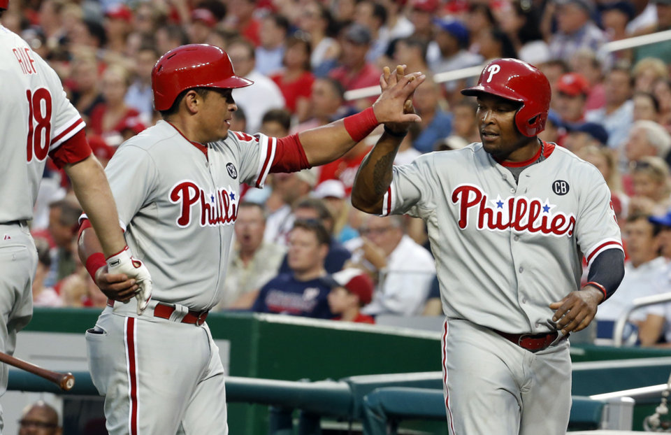 Photo - Philadelphia Phillies' Marlon Byrd, left, and catcher Carlos Ruiz celebrate scoring during the fourth inning of a baseball game against the Washington Nationals at Nationals Park Thursday, July 31, 2014, in Washington. (AP Photo/Alex Brandon)