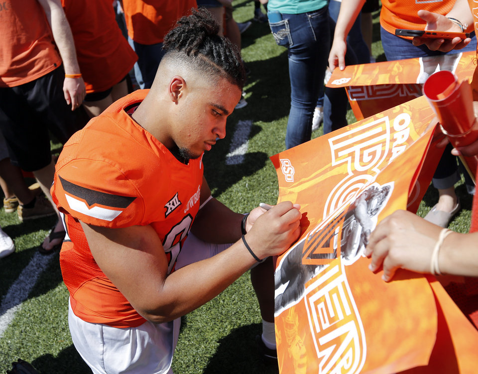Photo - Landon Wolf (88) autographs a poster for a fan after the spring football game for the Oklahoma State Cowboys (OSU) at Boone Pickens Stadium in Stillwater, Okla., Saturday, April 28, 2018. Photo by Nate Billings, The Oklahoman