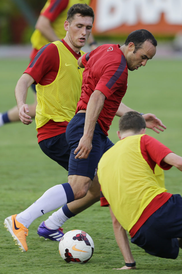 Photo - United States' Landon Donavan fights for the ball with Matt Besler, left, during a training session in Sao Paulo, Brazil, Tuesday, Jan. 14, 2014. The US national soccer team is on a training program in Sao Paulo preparing for the World Cup tournament, which gets underway on June. (AP Photo/Nelson Antoine)
