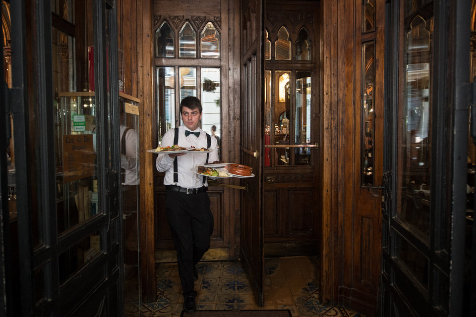 Photo - In this photo taken Monday, July 31, 2014, a waiter carries plates with food to customers at Caru cu Bere restaurant, Bucharest, Romania. Caru cu Bere, a fabled restaurant in the Old City, has been serving cold beer, spicy sausages and a lot more since the last year of the 19th century. (AP Photo/Octav Ganea) ROMANIA OUT