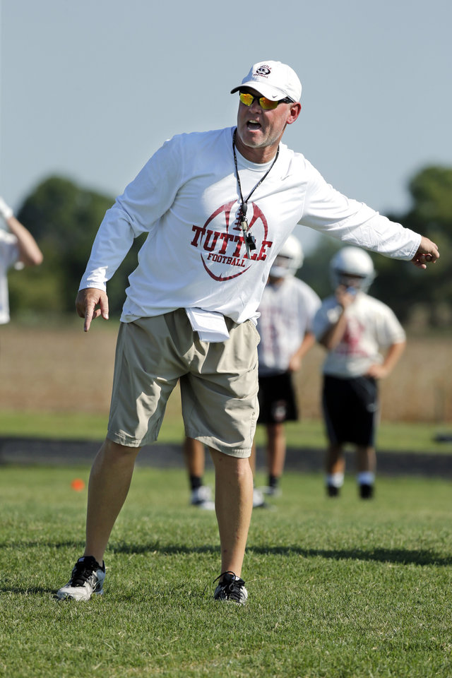 Photo - New head coach Brad Ballard works with players during high school football practice on Tuesday, Aug. 12, 2014 in Tuttle, Okla. Photo by Steve Sisney, The Oklahoman