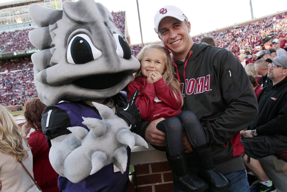 Sooner fans Ryan Jones and his daughter Ansley, 3, pose with the Horned Frogs mascot before a college football game between the University of Oklahoma Sooners (OU) and the TCU Horned Frogs at Gaylord Family-Oklahoma Memorial Stadium in Norman, Okla., on Saturday, Oct. 5, 2013. Photo by Steve Sisney, The Oklahoman