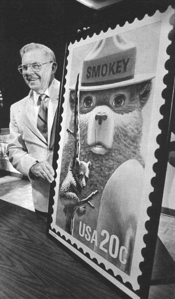 Photo - FILE - This Aug. 13, 1984 file photo shows Ray Bell, the man who cared for Smokey Bear after the young cub was rescued from a forest fire 50 years ago, is shown with an oversized copy of the Smokey Bear stamp during first day of issue ceremonies in Capitan, N.M. Smokey Bear is turning 70 on Saturday _ but don't bring any candles to the party, please. As the friendly, huggable bear with the brimmed hat and shovel enters his golden years, he's burning up Twitter, but his message of fire prevention through personal responsibility hasn't changed _ much.  (AP Photo/Albuquerque Journal, Eugene Burton, file)