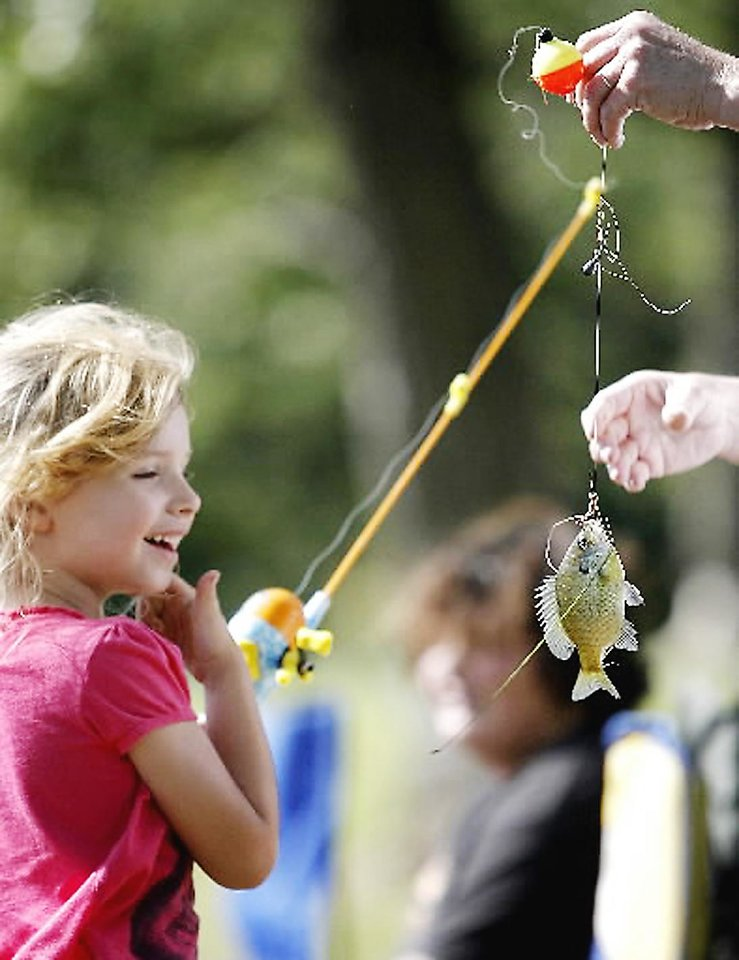 Photo - Sabra Frederick, 5, of Choctaw, gets help taking a fish off her line.