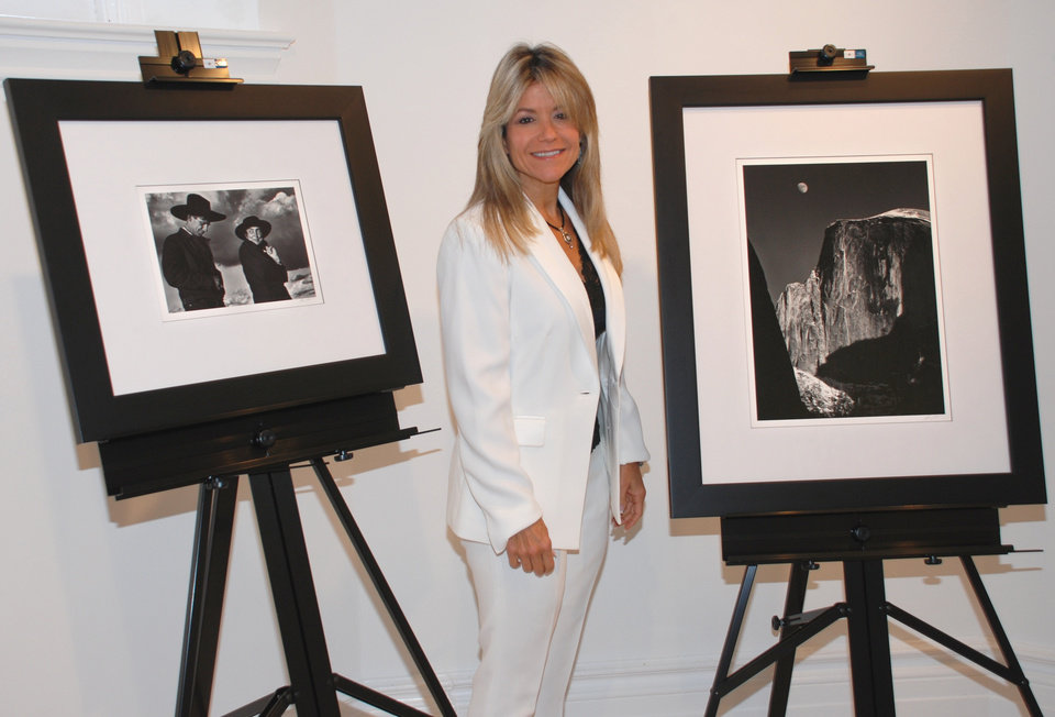 "In this photo provided by the College of New Rochelle, Judith Huntington, president of The College of New Rochelle, is flanked by two Ansel Adams photographs at the school in New Rochelle, Tuesday, Oct. 9, 2012. The two photos are from a collection of 75 signed Ansel Adams photographs, valued at $2.5 million, that were a gift to the school. At left is ""Georgia O'Keefe and Orville Cox, Canyon de Chellly National Monument, Arizona, 1937,"" and at right ""Moon and Half Dome, Yosemite National Park, California, 1960."" (AP Photo/College of New Rochelle)"