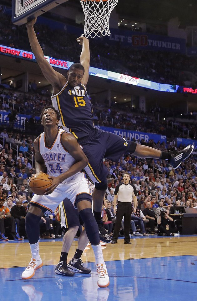 Photo - Oklahoma City Thunder's Hasheem Thabeet (34) is fouled by Utah Jazz's Derrick Favors (15) during the NBA basketball game between the Oklahoma City Thunder and the Utah Jazz at Chesapeake Energy Arena on Wednesday, March 13, 2013, in Oklahoma City, Okla. Photo by Chris Landsberger, The Oklahoman