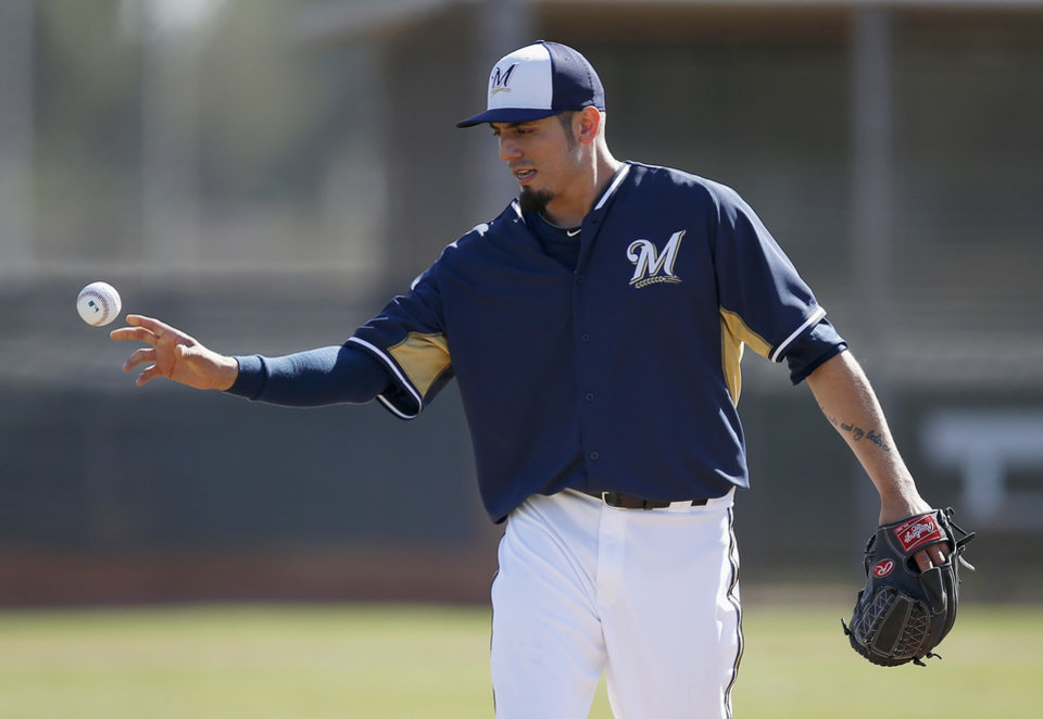 Photo - Milwaukee Brewers' Matt Garza flips a baseball into a bucket after covering first base on an infield grounder during Brewers spring training baseball practice, Monday, Feb. 17, 2014, in Phoenix. (AP Photo/Ross D. Franklin)