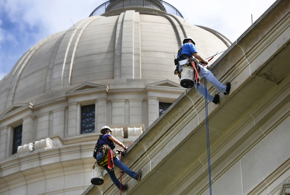 Photo -                    Sarah Sinusas, left, and Steve Naggatz, engineers with WJE Architects and Engineers, hang nearly 60 feet above the ground as they step off the ledge of the state Capitol during an inspection of the building in September. The Oklahoma Supreme Court on Monday struck down a legal challenge to the bond issue that will pay for repairs to the Capitol.                     PHOTO BY JIM BECKEL, THE OKLAHOMAN ARCHIVES