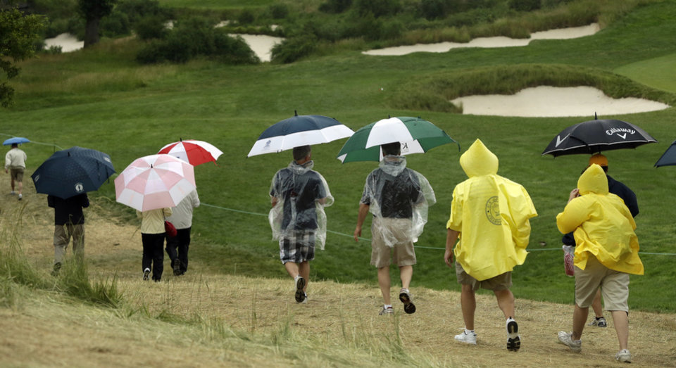 Photo - Spectators walk off the course as a weather warning delays the first round of the U.S. Open golf tournament at Merion Golf Club, Thursday, June 13, 2013, in Ardmore, Pa. (AP Photo/Gene J. Puskar)