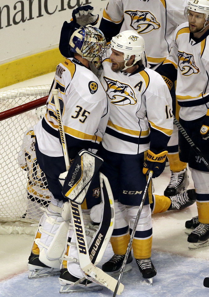 Photo - Nashville Predators goalie Pekka Rinne (35) celebrates with Mike Fisher (12) after they defeated the Chicago Blackhawks 3-2 during an NHL hockey game in Chicago, Friday, March 14, 2014. (AP Photo/Nam Y. Huh)