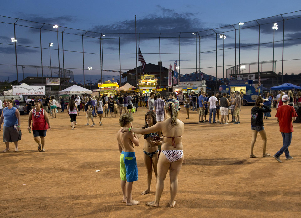 Festival goers crowd the infield-turned-food court as the sun sets during the Fourth of July celebration at Pioneer Park, Thursday, July 4, 2013 in Prescott, Ariz.  On a day meant to ponder the nation's birth, and those who built and defended it over 237 years, Prescott's residents had 19 of their neighbors, their friends, their relatives to remember. Nineteen Granite Mountain Hotshot firefighters were killed Sunday by an out-of-control blaze near Yarnell, Ariz. (AP Photo/Julie Jacobson)