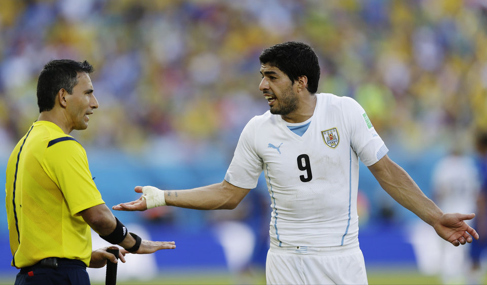 Photo - Uruguay's Luis Suarez argues with referee Marco Rodriguez from Mexico during the group D World Cup soccer match between Italy and Uruguay at the Arena das Dunas in Natal, Brazil, Tuesday, June 24, 2014. (AP Photo/Ricardo Mazalan)