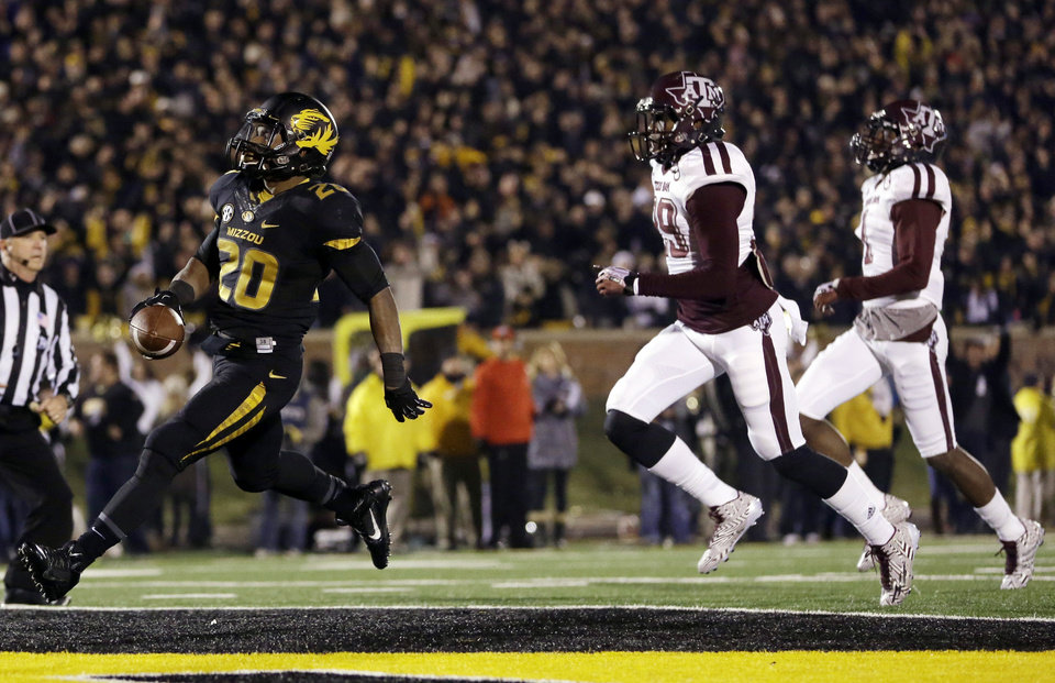 Photo - Missouri running back Henry Josey, left, scores on a 57-yard run as Texas A&M defensive backs Deshazor Everett and De'Vante Harris, right, give chase during the second half of an NCAA college football game on Saturday, Nov. 30, 2013, in Columbia, Mo. (AP Photo/Jeff Roberson)