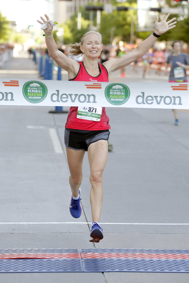 Photo -  Stephanie Andre celebrates as she breaks the tape at the finish line to win the women's division of the Oklahoma City Memorial Marathon. Andre set a new state record in the women's marathon. [Bryan Terry/The Oklahoman]