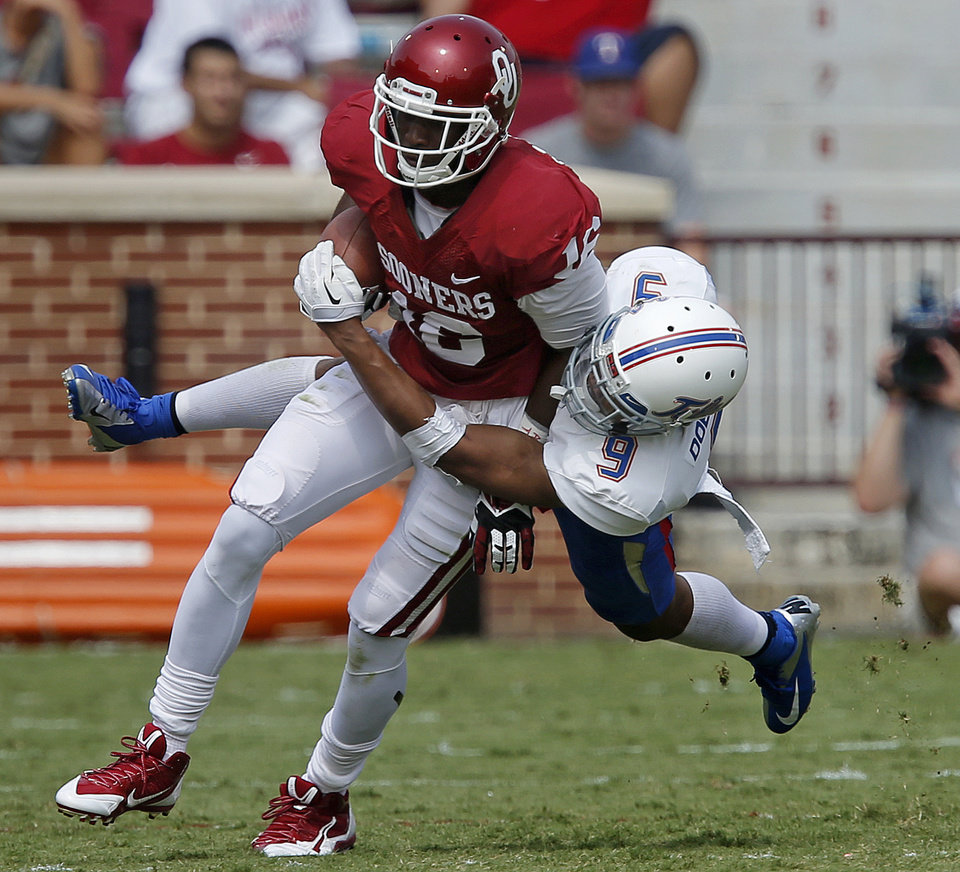 Photo - Oklahoma's Jaz Reynolds (16) tries to fight off Tulsa's Dwight Dobbins (9) during a college football game between the University of Oklahoma Sooners (OU) and the Tulsa Golden Hurricane at Gaylord Family-Oklahoma Memorial Stadium in Norman, Okla., on Saturday, Sept. 14, 2013. Oklahoma won 51-20. Photo by Bryan Terry, The Oklahoman