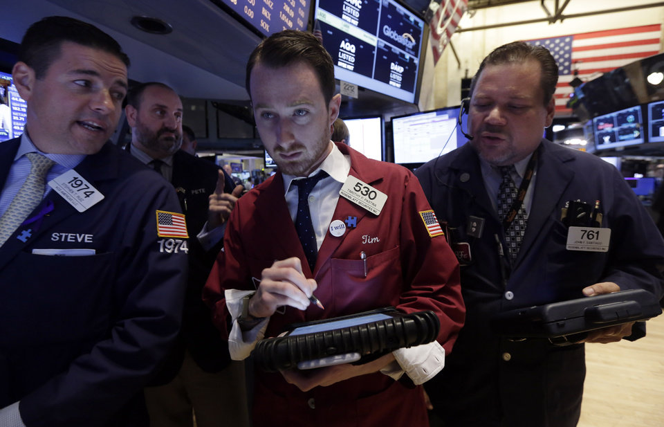 Photo - Specialist Stephen Ruiz, left, works with traders Timothy Pastina, center, and John Santiago, right, on the floor of the New York Stock Exchange, Wednesday, June 18, 2014. U.S. stocks are little changed in early trading as investors wait for the latest policy action from the Federal Reserve. (AP Photo/Richard Drew)