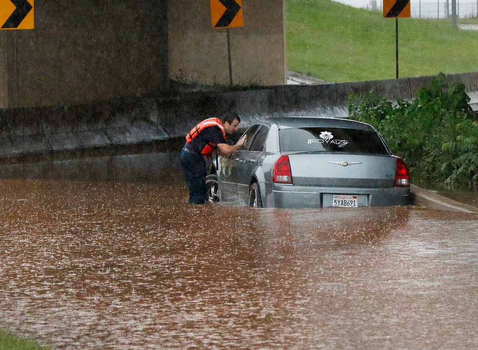 Photo - An Oklahoma City firefighter checks for occupants inside this vehicle that became stranded in high water on the northbound ramp to I-235 from NW 23 Street. Brief periods of heavy rain caused road flooding and created hazardous driving conditions around 7 pm Saturday, May 23, 2015.  Oklahoma City police used their vehicles to barricade all directions of traffic at NW 23 and Broadway, preventing vehicles from driving into high and rushing water. Photo by Jim Beckel, The Oklahoman.
