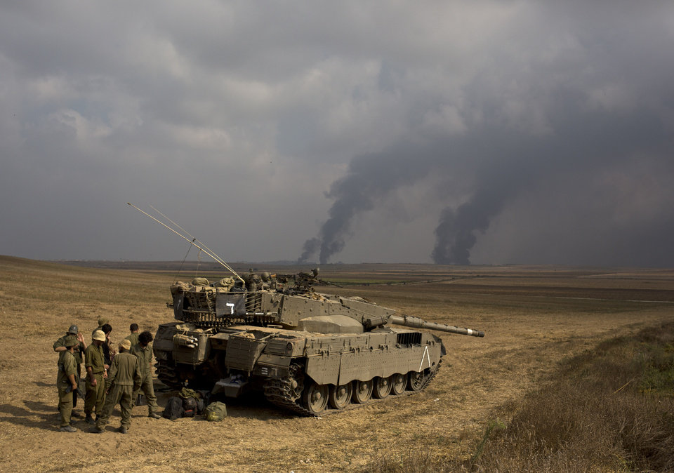 Photo - Israeli soldiers stand behind a tank as heavy smoke rises from the Gaza Strip Tuesday, July 22, 2014. Israeli airstrikes pummeled a wide range of targets in the Gaza Strip on Tuesday as the U.N. chief and the U.S. secretary of state began an intensive effort to end more than two weeks of fighting that has killed hundreds of Palestinians and tens of Israelis. (AP Photo/Tsafrir Abayov)