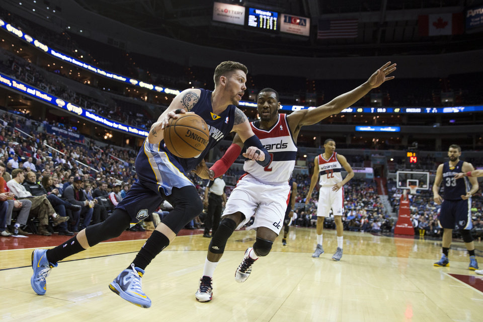 Photo - Memphis Grizzlies forward Mike Miller, left, drives past Washington Wizards guard John Wall during the first half of an NBA basketball game on Monday, March 3, 2014, in Washington. (AP Photo/ Evan Vucci)