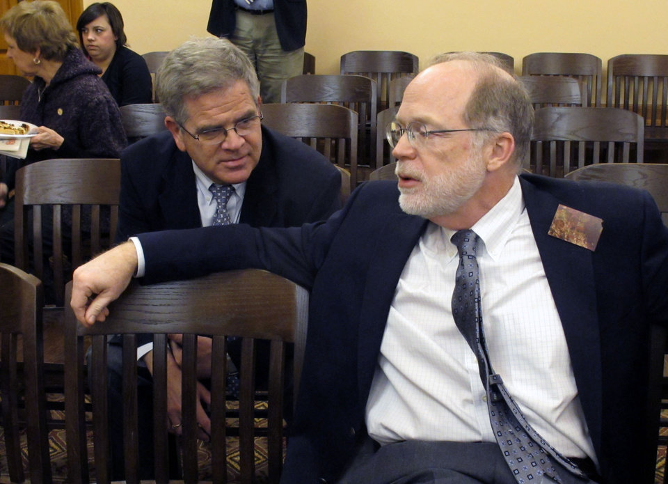 Photo - Kansas Hospital Association lobbyists Bill Brady, left, and Tom Bell, right, talk while they wait for the state House Appropriations Committee to take up a resolution opposing an expansion of Medicaid under the federal health care overhaul, Friday, Feb. 22, 2013, at the Statehouse in Topeka, Kan. Bell, also the association's president, has testified against the measure. (AP Photo/John Hanna)