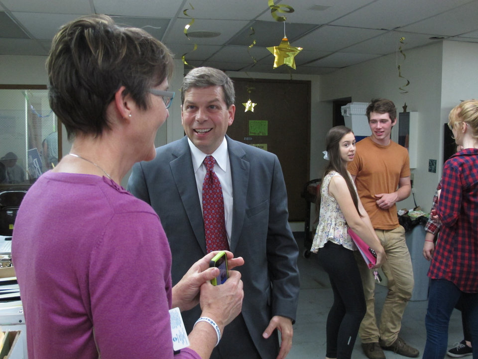 Photo - U.S. Sen. Mark Begich, D-Alaska, speaks with a woman at his campaign's volunteer office in Anchorage, Alaska, on Monday, Aug. 18, 2014. (AP Photo/Becky Bohrer)