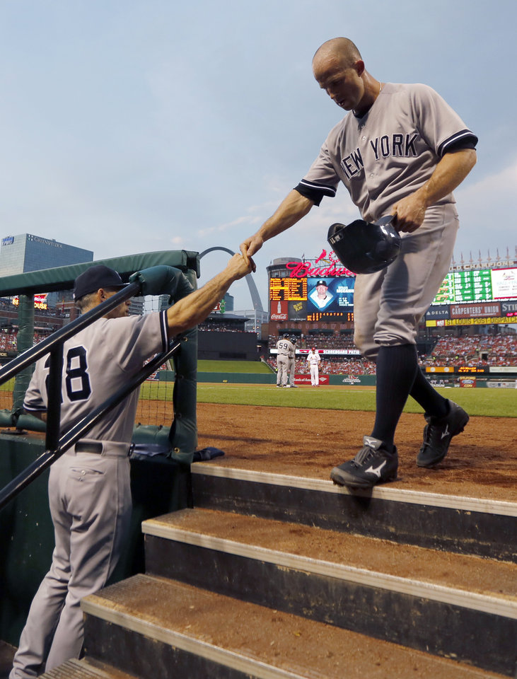 Photo - New York Yankees' Brett Gardner, right, is congratulated by manager Joe Girardi after scoring on a single by Jacoby Ellsbury during the third inning of a baseball game against the St. Louis Cardinals on Wednesday, May 28, 2014, in St. Louis. (AP Photo/Jeff Roberson)