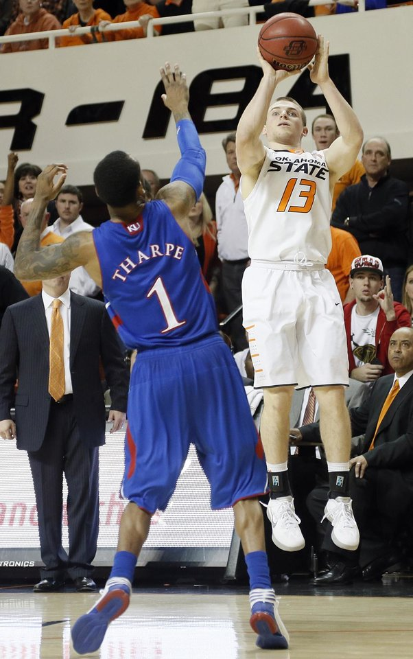 Photo - Oklahoma State 's Phil Forte (13) shoots the ball over Kansas' Naadir Tharpe (1) during the college basketball game between the Oklahoma State University Cowboys (OSU) and the University of Kanas Jayhawks (KU) at Gallagher-Iba Arena on Wednesday, Feb. 20, 2013, in Stillwater, Okla. Photo by Chris Landsberger, The Oklahoman