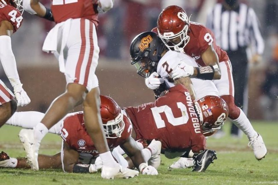 Photo -  Oklahoma's D.J. Graham (9) and David Ugwoegbu (2) bring down Oklahoma State's Tylan Wallace (2) during a bedlam college football game between the University of Oklahoma Sooners (OU) and the Oklahoma State Cowboys (OSU) at Gaylord Family-Oklahoma Memorial Stadium in Norman, Okla., Saturday, Nov. 21, 2020. Oklahoma won 41-13. [Bryan Terry/The Oklahoman]