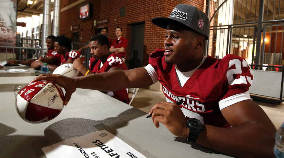 Photo - Defensive back Kass Everett hands a ball back to a fan during fan appreciation day for the University of Oklahoma Sooner (OU) football team at Gaylord Family-Oklahoma Memorial Stadium in Norman, Okla., on Saturday, Aug. 3, 2013. Photo by Steve Sisney, The Oklahoman