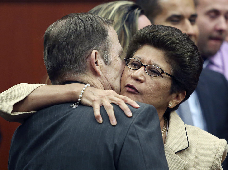 Photo - George Zimmerman's parents Robert Zimmerman Sr. and Gladys Zimmerman embrace following George Zimmerman's not guilty verdict in Seminole Circuit Court in Sanford, Fla., on Saturday, July 13, 2013. Jurors found Zimmerman not guilty of second-degree murder in the fatal shooting of unarmed 17-year-old Trayvon Martin in Sanford. The six-member, all-woman jury deliberated for more than 15 hours over two days before reaching their decision Saturday night. (AP Photo/Gary W. Green, Pool) ORG XMIT: FLJR403