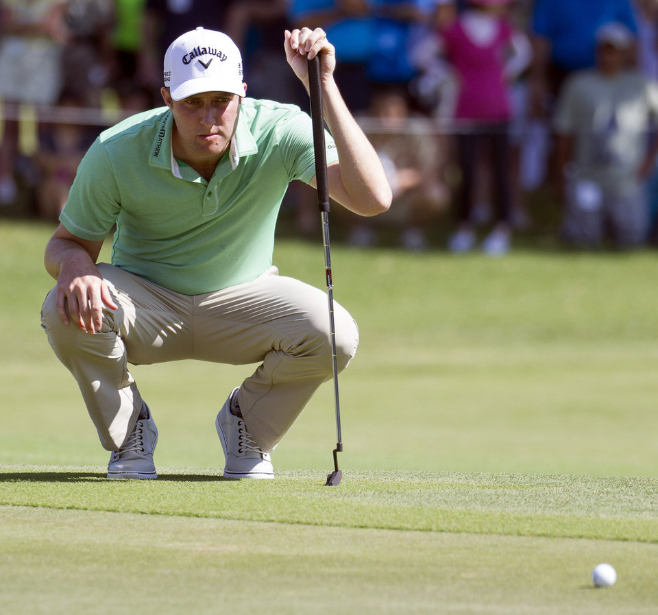 Photo - Chris Kirk lines up his putt on the first green during the fourth round of the Sony Open golf tournament at Waialae Country Club, Sunday, Jan. 12, 2014, in Honolulu. (AP Photo/Eugene Tanner)