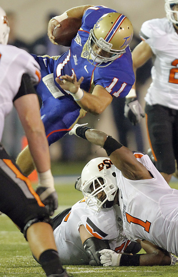 Oklahoma State's Joseph Randle (1) upends Tulsa's Alan Dock (11) after an interception during a college football game between the Oklahoma State University Cowboys and the University of Tulsa Golden Hurricane at H.A. Chapman Stadium in Tulsa, Okla., Sunday, Sept. 18, 2011. Photo by Chris Landsberger, The Oklahoman