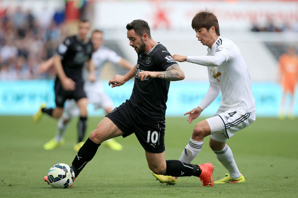 Photo - Burnley's Danny Ings battles for the ball with Swansea City's Ki Sung-Yueng during the English Premier League match at the Liberty Stadium, Swansea, Wales, Saturday Aug. 23, 2014. (AP Photo/PA, Nick Potts)  UNITED KINGDOM OUT  NO SALES  NO ARCHIVE