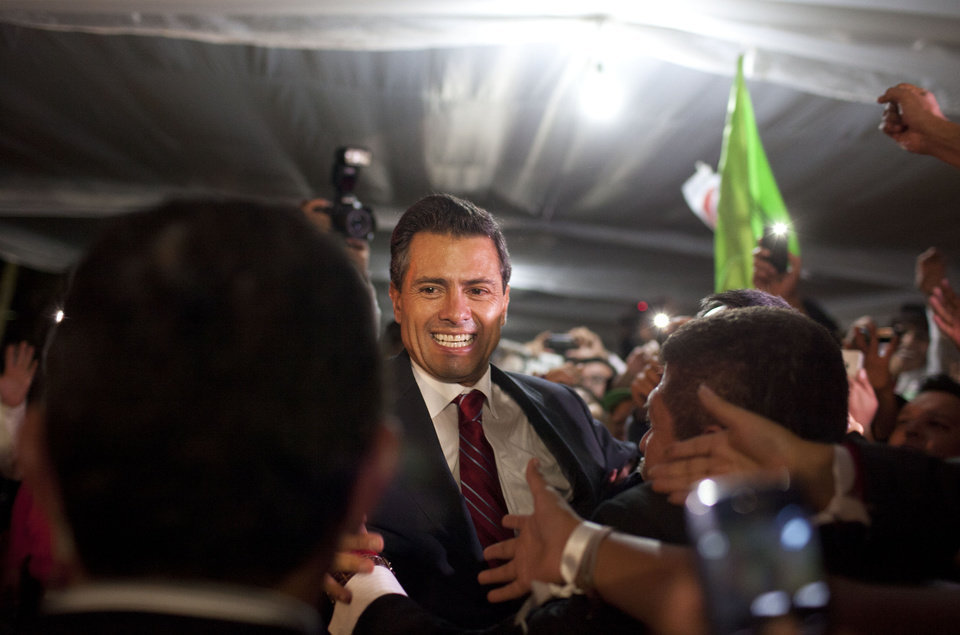Photo -   Enrique Pena Nieto, presidential candidate for the Revolutionary Institutional Party (PRI), greets supporters at his party's headquarters in Mexico City, early Monday, July 2, 2012. Mexico's old guard sailed back into power after a 12-year hiatus Sunday as the official preliminary vote count handed a victory to Pena Nieto, whose party was long accused of ruling the country through corruption and patronage. (AP Photo/Alexandre Meneghini)