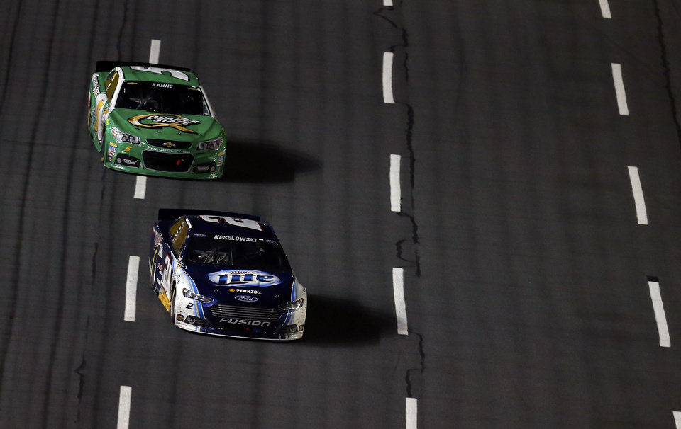 Photo - Brad Keselowski (2) drives past Kasey Kahne (5) during the NASCAR Sprint Cup Series auto race at Charlotte Motor Speedway in Concord, N.C., Saturday, Oct. 12, 2013. (AP Photo/Chris Keane)