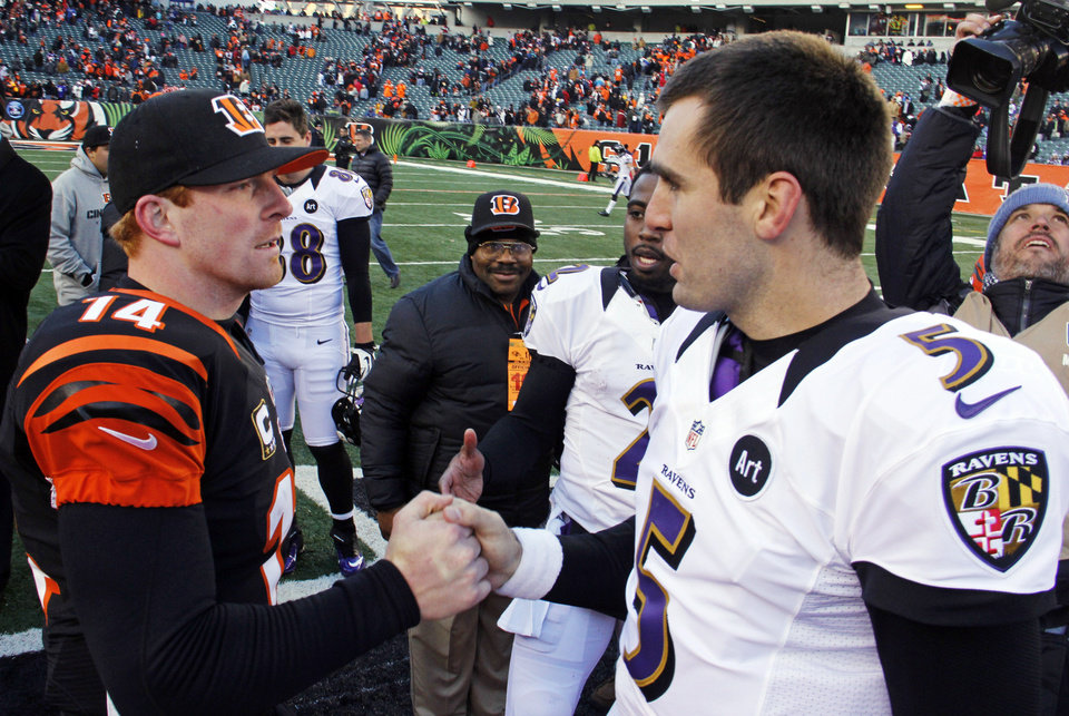 Photo - Cincinnati Bengals quarterback Andy Dalton (14) greets Baltimore Ravens quarterback Joe Flacco (5) after the Bengals' 23-17 win in an NFL football game, Sunday, Dec. 30, 2012, in Cincinnati. (AP Photo/Tom Uhlman)