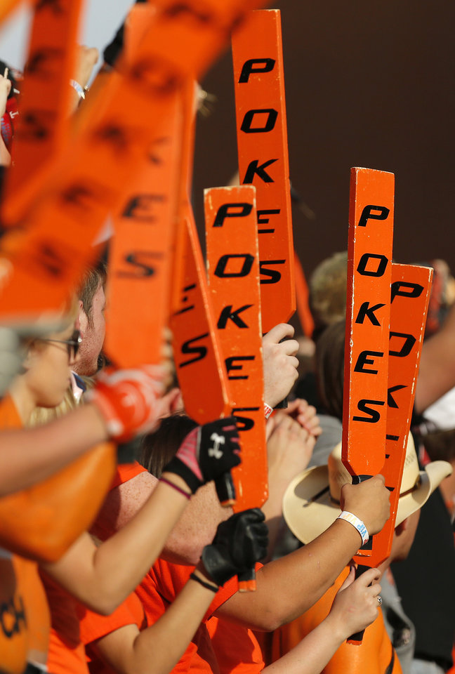 Photo - The OSU Paddle People raise their paddles during a college football game between Oklahoma State University (OSU) and West Virginia University (WVU) at Boone Pickens Stadium in Stillwater, Okla., Saturday, Nov. 10, 2012. Photo by Nate Billings, The Oklahoman
