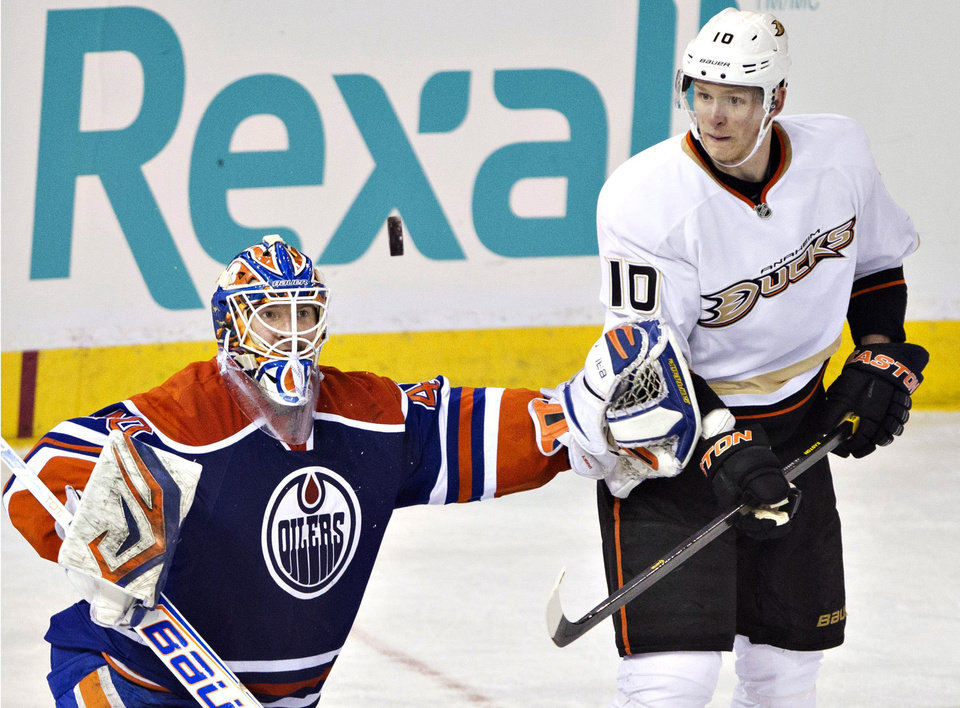 Photo - Anaheim Ducks' Corey Perry (10) looks for the rebound as Edmonton Oilers goalie Devan Dubnyk makes the save during the second period of their NHL hockey game in Edmonton, Alberta, Sunday, April 21, 2013. (AP Photo/The Canadian Press, Jason Franson)