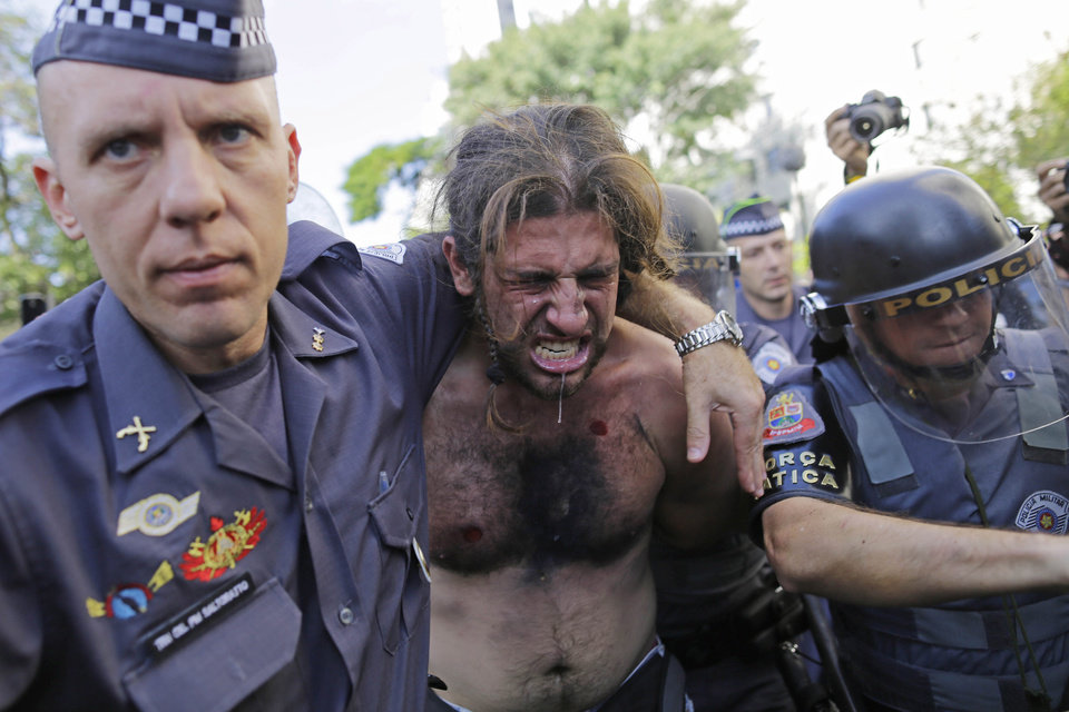 Photo - FILE - In this June 12, 2014, file photo, a protester is detained by police during a demonstration demanding better public services and protesting the money spent on the World Cup soccer tournament in Sao Paulo, Brazil. Brazil avoided a repeat of last year's Confederations Cup when violent protests broke out in several cities and more than a million Brazilians took to the streets. But the absence of conflict during the World Cup was less a result of dissipated public anger than of attention being glued to the games, and police acting quickly to crack down on even small demonstrations. (AP Photo/Nelson Antoine, File)