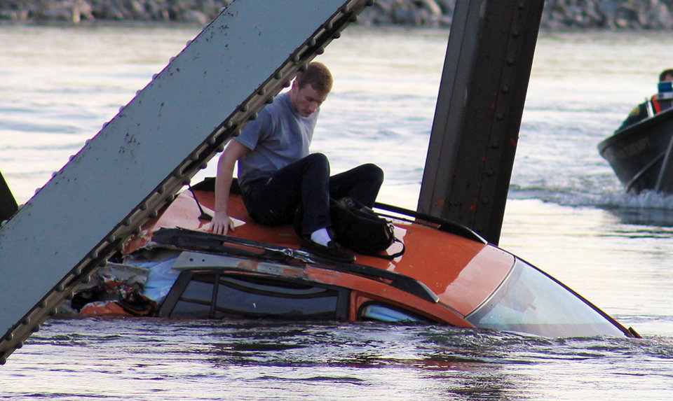 In this photo provided by Francisco Rodriguez, Bryce Kenning sits atop his car that fell into the Skagit River after the collapse of the Interstate 5 bridge there minutes earlier Thursday, May 23, 2013, in Mount Vernon, Wash. (AP Photo/Francisco Rodriguez)