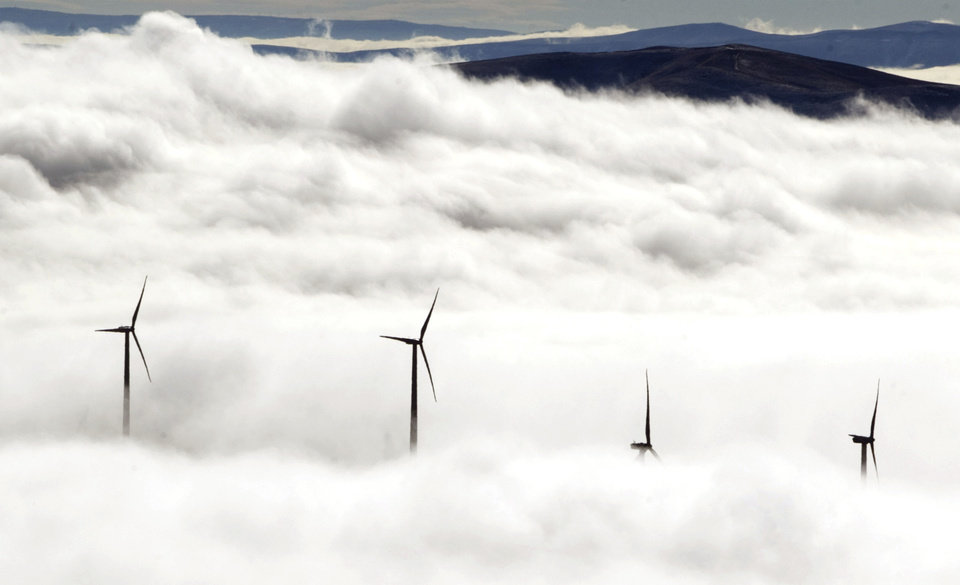 Photo - FILE- In this Nov. 14, 2012, file photo, wind turbines at the Vantage Wind Farm stand above the clouds at Vantage, Wash.  Renewable energy is derived from renewable sources such as wind, solar, geothermal or plant matter. This type of energy is growing fast in the U.S., but it remains a small contributor to the nation's energy mix. (AP Photo/Yakima Herald-Republic, Gordon King, File)