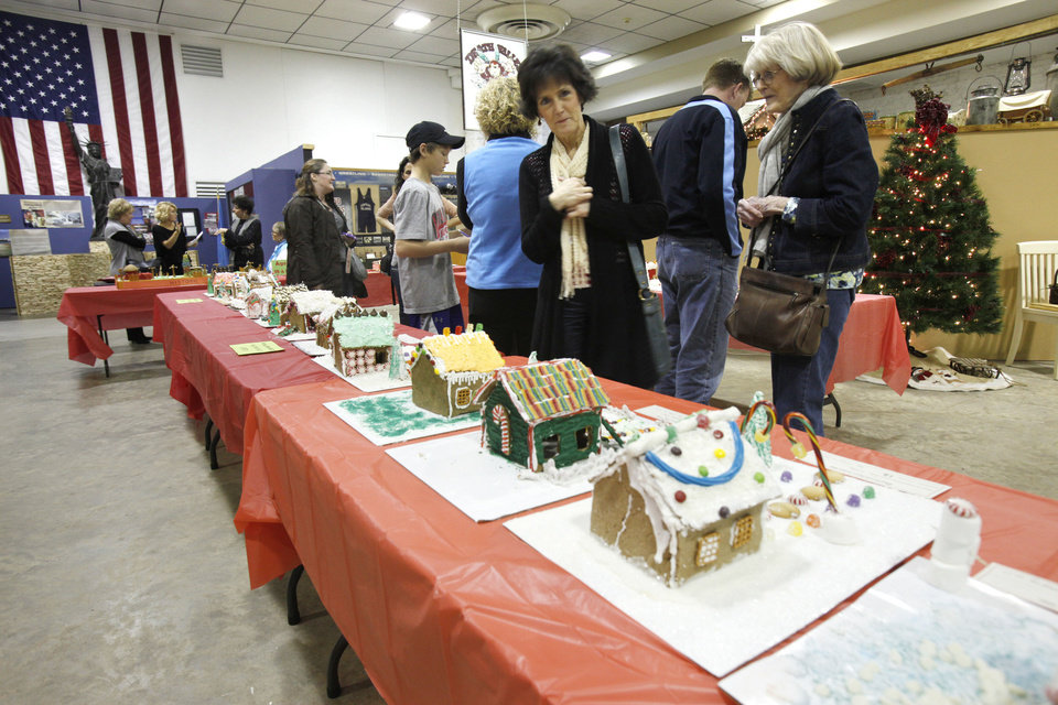 Spectators look at ginerbread creations during the fourth annual gingerbread house contest at the Edmond Historical Society and Museum. PHOTO BY PAUL HELLSTERN, THE OKLAHOMAN. <strong>PAUL HELLSTERN - THE OKLAHOMAN</strong>